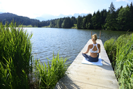 Germany, Mittenwald, back view of woman practising yoga on jetty at lake - ECPF00232