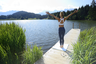 Germany, Mittenwald, back view of woman practising yoga on jetty at lake - ECPF00235