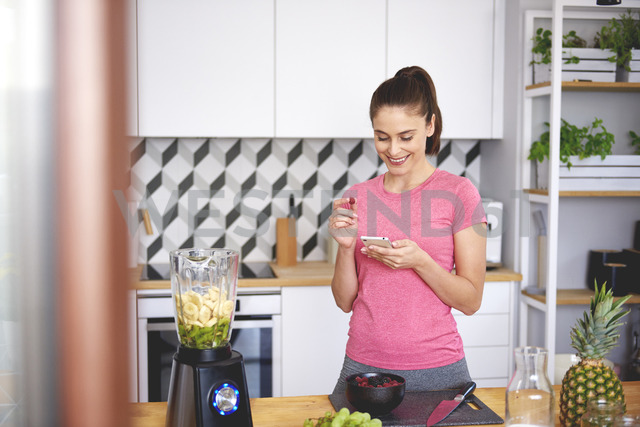 Smiling young woman looking at cell phone in the kitchen - ABIF00781