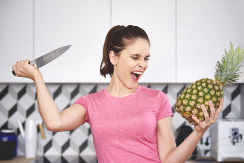 Portrait of screaming woman attacking pineapple with knife in the kitchen - ABIF00787