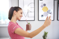 Smiling young woman with smoothie taking selfie with smartphone in the kitchen - ABIF00799