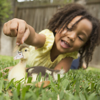 A young girl lying on the grass stroking the head of a duckling. - MINF03017
