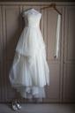 Wedding dress hanging on a wardrobe door, wedding shoes on the floor. - MINF03080