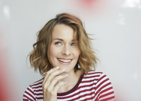 Portrait of smiling woman wearing red-white striped t-shirt - PNEF00776