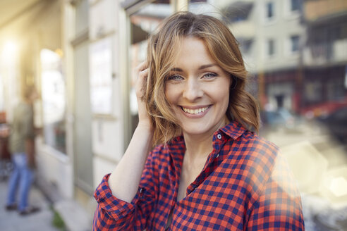Portrait of smiling woman in the city - PNEF00785