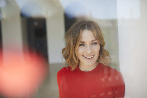 Portrait of smiling woman wearing red shirt looking out of window - PNEF00791