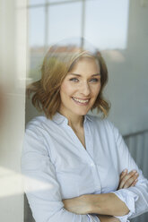 Portrait of smiling businesswoman  behind windowpane - PNEF00797