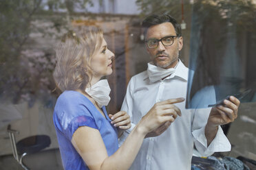Portrait of radiologist and nurse behind windowpane looking at x-ray image - PNEF00818