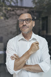 Portrait of man with stubble behind windowpane wearing white shirt and glasses - PNEF00821
