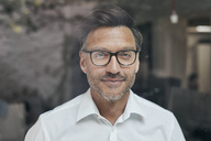 Portrait of man with stubble behind windowpane wearing white shirt and glasses - PNEF00824