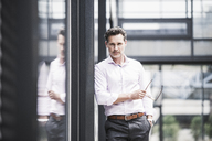 Portrait of confident businessman outside office building - UUF14672