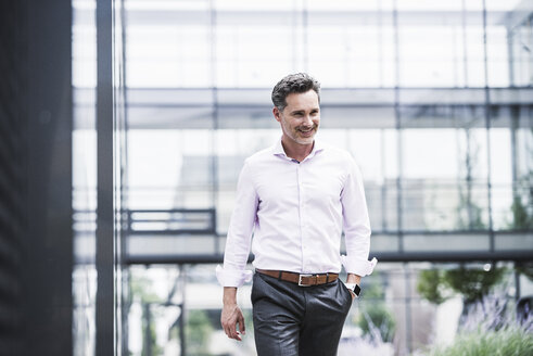 Smiling businessman walking outside office building - UUF14678