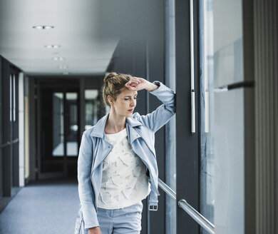 Businesswoman leaning against window in office passageway - UUF14693