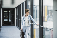 Businesswoman looking out of window in office passageway - UUF14696
