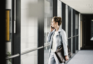 Businesswoman on cell phone looking out of window in office passageway - UUF14699