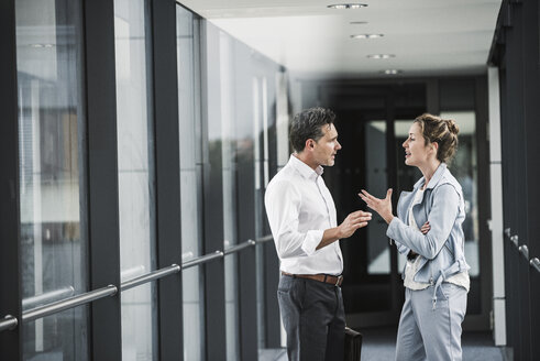 Businesswoman and businessman discussing in office passageway - UUF14702