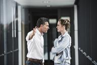 Businesswoman and businessman arguing in office passageway - UUF14705