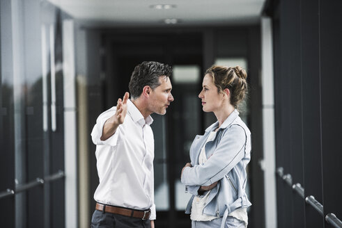 Businesswoman and businessman arguing in office passageway - UUF14705