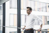 Businessman leaning on railing in office building - UUF14726