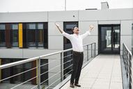 Cheering businessman standing on skywalk at office building - UUF14729