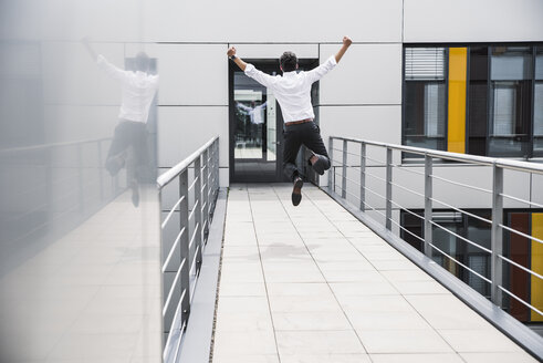 Cheering businessman jumping on skywalk at office building - UUF14732