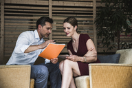 Businesswoman and businessman discussing in office lounge - UUF14756
