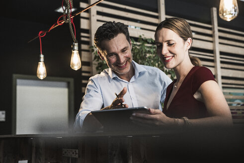 Smiling businesswoman and businessman with tablet discussing in office - UUF14759