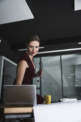Businesswoman in office with laptop and plan on desk - UUF14768