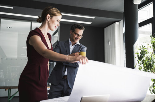 Businesswoman presenting plan to businessman in office at desk - UUF14774