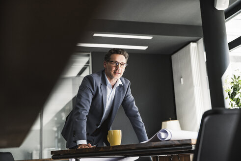 Businessman in office with plan on desk - UUF14780