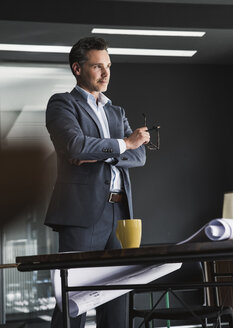 Businessman standing in office with plan on desk - UUF14783