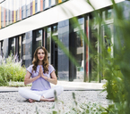 Woman practicing yoga in garden outsde office building - UUF14786