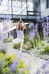 Woman practicing yoga in garden outsde office building - UUF14792