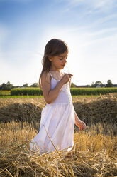 Little girl standing in havested field smelling flower - LVF07353
