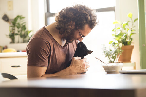 Young man cuddling his black cat at home - MFRF01156