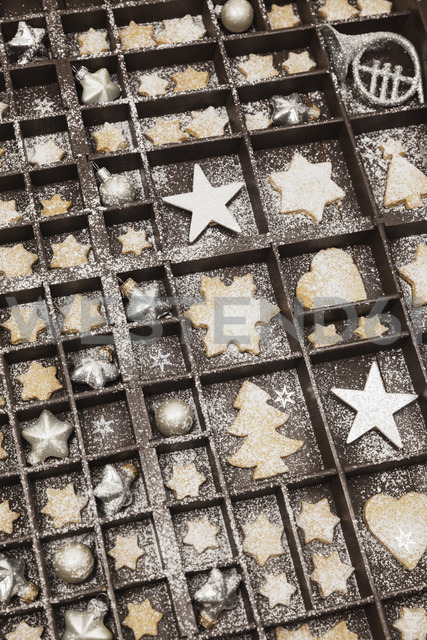 Homemade Christmas cookies, stars and Christmas baubles in old wooden typecase - GWF05614