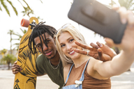 Portrait of multicultural young couple taking selfie with smartphone - WPEF00715
