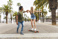 Spain, Barcelona, young man teaching his girlfriend skateboarding - WPEF00721
