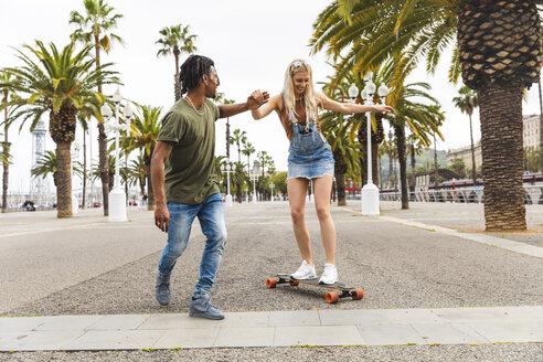 Spain, Barcelona, young man teaching his girlfriend skateboarding - WPEF00721