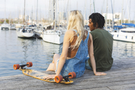 Spain, Barcelona, multicultural young couple with longboard relaxing at harbour - WPEF00733
