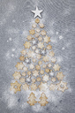 Star-shaped biscuits and Christmas baubles forming Christmas Tree on grey background - GWF05616