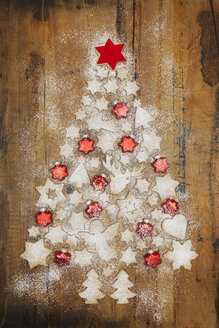 Christmas cookies and red star-shaped Christmas baubles forming Christmas Tree on wooden background - GWF05619