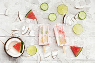 Homemade watermelon coconut ice lollies with lime and cucumber slices, fresh coconut and watermelon pieces on ice cubes - GWF05625