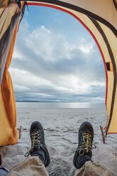 Feet of man, lying in tent on beach - VPIF00415