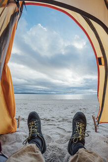 Feet of man, lying in tent on beach - VPIF00415
