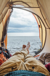 Feet of man, lying in tent on beach - VPIF00418