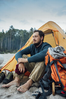 Backpacker sitting in front of his tent on the beach - VPIF00421