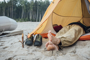 Man lying in tent on beach - VPIF00424