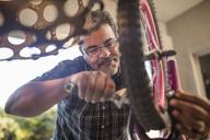 Man fixing wheel of children's bicycle - ZEF15909
