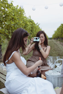 Friends having picnic in a vineyard, one woman taking pictures with instant camera - MAUF01625
